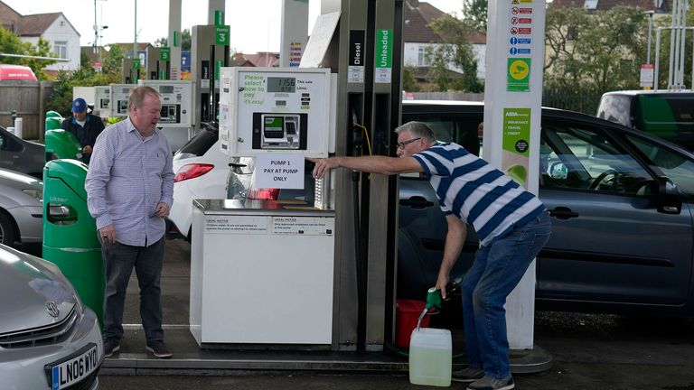 A man filled up a canister at a busy petrol station in London, Monday, Oct. 4, 2021. British military personnel have begun delivering fuel to gas stations after a shortage of truck drivers disrupted supplies for more than a week, leading to long lines at the pumps as anxious drivers scrambled to fill their tanks. (AP Photo/Frank Augstein) PIC:AP