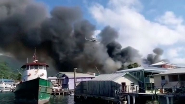 Smoke billows from a fire at a residential area on the island of Guanaja, Honduras