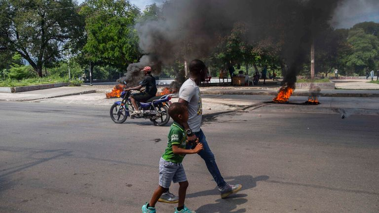 A man and a child walk by burning tires on a street in Port-au-Prince, Haiti, Sunday, Oct. 17, 2021. A group of 17 U.S. missionaries including children was kidnapped by a gang in Haiti on Saturday, Oct. 16, according to a voice message sent to various religious missions by an organization with direct knowledge of the incident.