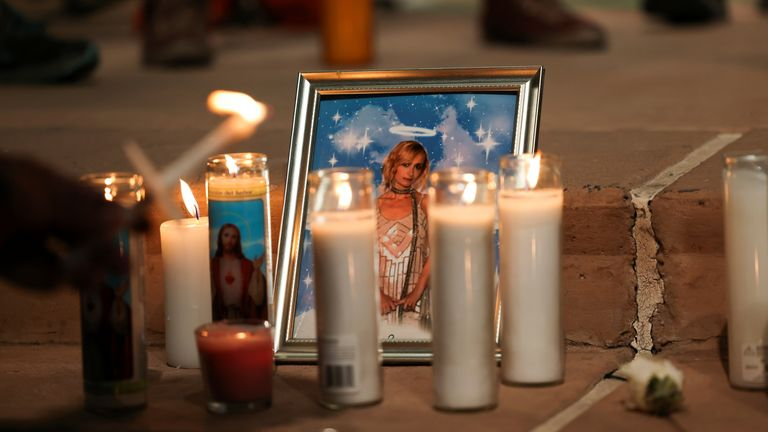 """A photo of cinematographer Halyna Hutchins, who died after being shot by Alec Baldwin on the set of his movie """"Rust"""", rests among candles at a vigil in Albuquerque, New Mexico, U.S., October 23, 2021. REUTERS/Kevin Mohatt"""