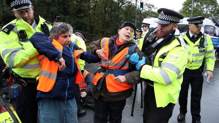 Police officers detain Insulate Britain activists blocking a motorway junction near Heathrow Airport, in London, Britain, October 1, 2021. REUTERS/Peter Cziborra