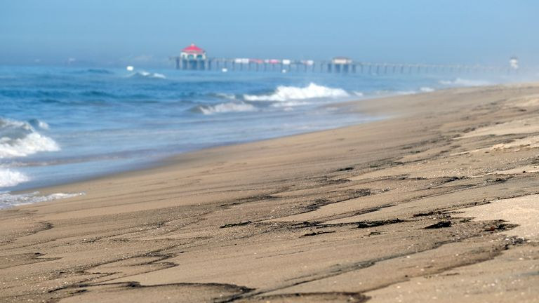 Patches of an oil spill wash off the beach south of the Pier in Huntington Beach, Calif., Sunday, Oct. 3, 2021. Pic: AP