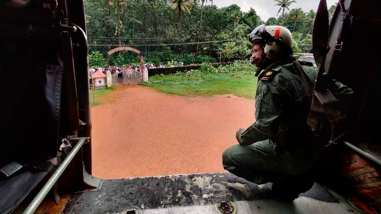This photograph provided by the Indian Navy shows a navy person looking from their helicopter on a mission to distribute relief material to flood affected people at Koottickal in Kottayam district, southern Kerala state