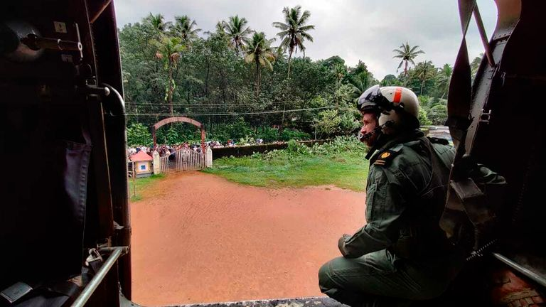 A navy airman looks out at Koottickal in Kottayam district, southern Kerala while on a mission to distribute relief material to flood affected people. Pic: AP