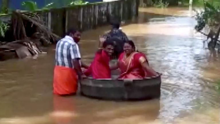 A bride and groom float to a temple in a cooking vessel on a flooded road for their wedding ceremony