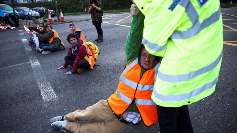 A police officer detains an Insulate Britain activist blocking a roundabout at a junction on the M25 motorway as they a protest in Thurrock, Britain October 13, 2021. REUTERS/Henry Nicholls