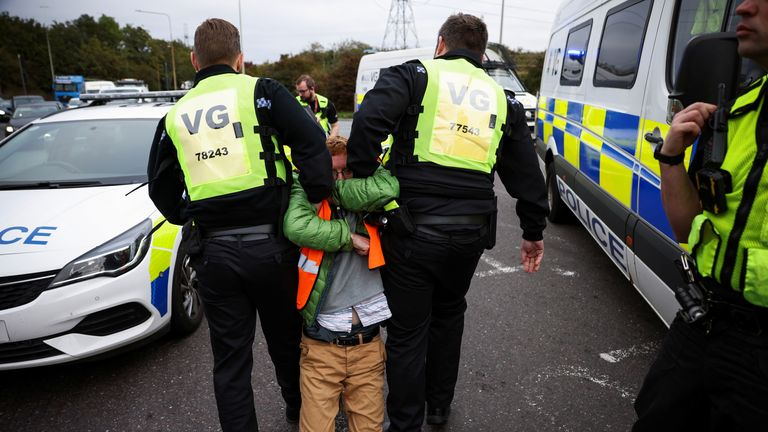 Police officers detain a demonstrator as Insulate Britain activists block a roundabout at a junction on the M25 motorway during a protest in Thurrock, Britain October 13, 2021. REUTERS/Henry Nicholls