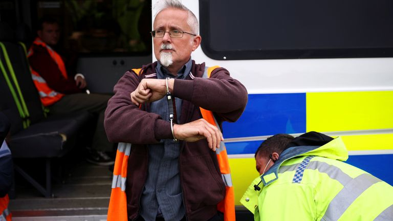 An Insulate Britain activist is handcuffed as demonstrators block a roundabout at a junction on the M25 motorway during a protest in Thurrock, Britain October 13, 2021. REUTERS/Henry Nicholls