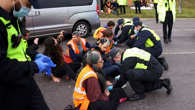 Police officers try to remove hands of Insulate Britain activists glued to the ground as they block a roundabout at a junction on the M25 motorway during a protest in Thurrock, Britain October 13, 2021. REUTERS/Henry Nicholls