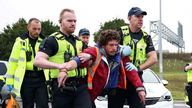 Police officers detain an Insulate Britain activist blocking a roundabout at a junction on the M25 motorway as they a protest in Thurrock, Britain October 13, 2021. REUTERS/Henry Nicholls