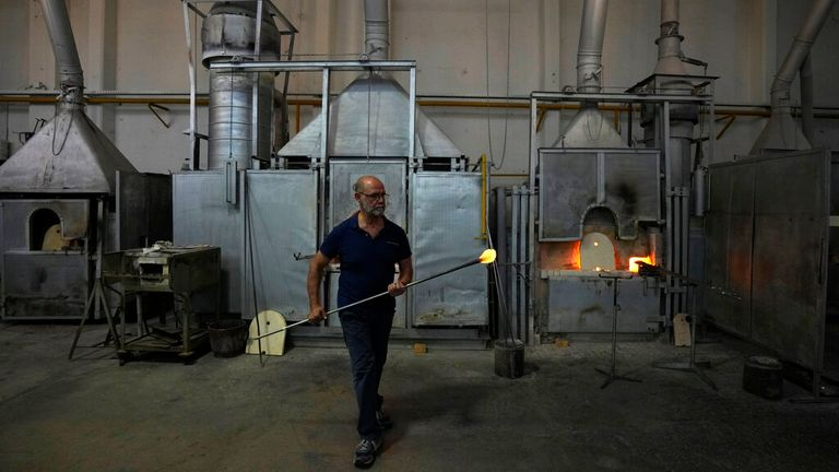 A glass-worker works at a glass artistic creation as he walks past methane powered ovens in a factory in Murano island, Venice. Pic: AP