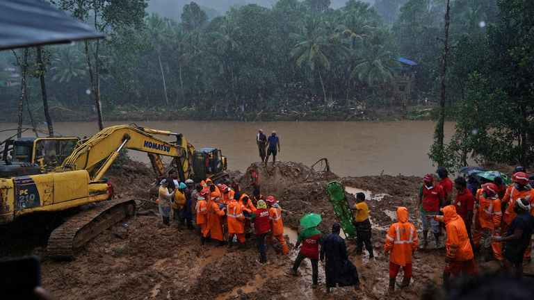 Rescue workers carry the body of a victim after recovering it from the debris of a residential house following a landslide caused by heavy rainfall at Kokkayar village in Idukki district in the southern state of Kerala