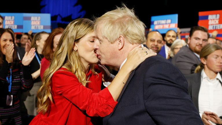Britain's Prime Minister Boris Johnson and his wife Carrie Johnson embrace ahead of his speech during the annual Conservative Party Conference, in Manchester, Britain, October 6, 2021. REUTERS/Phil Noble