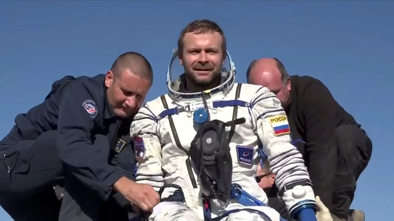 Russian film director Klim Shipenko is assisted by ground personnel shortly after landing. Pic: Roscosmos via Reuters