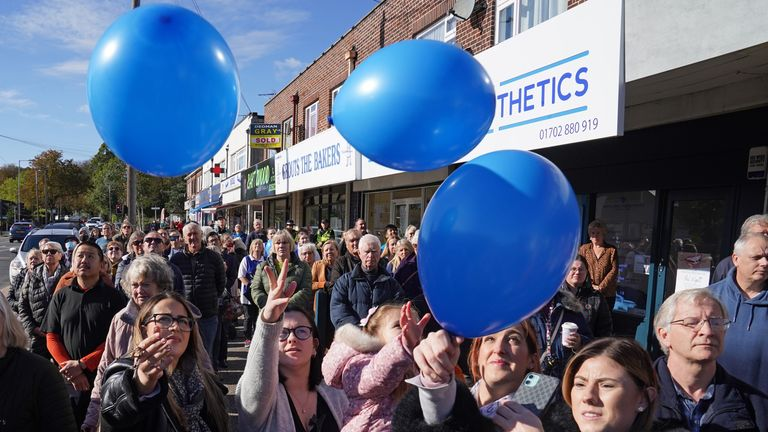 Shopkeepers and local residents release balloons as they gather to observe a two-minute silence in memory of MP Sir David Amess in Eastwood Road North in Leigh-on-Sea, Essex. Ali Harbi Ali is appearing in the dock at the Old Bailey in London charged with the terrorism-related murder of the Southend West MP. Picture date: Friday October 22, 2021.