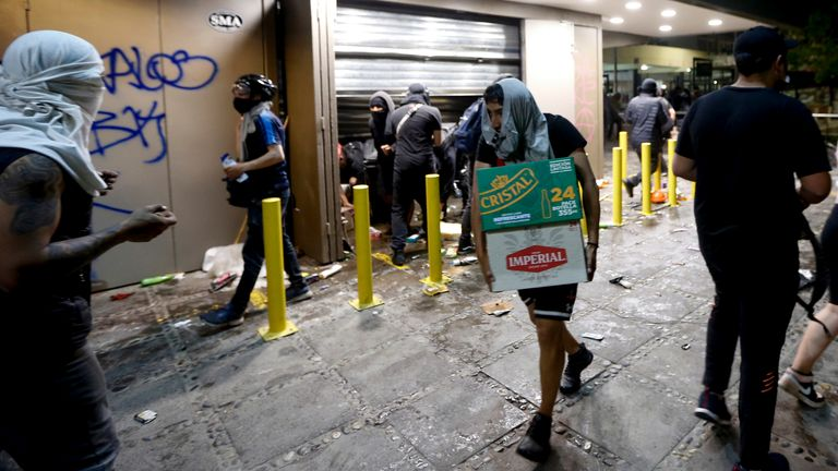 People loot a supermarket on the two-year anniversary of the start of anti-government mass protests over inequality, in Santiago, Chile, Monday, Oct. 18, 2021. (AP Photo/Luis Hidalgo) PIC:AP