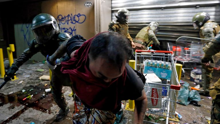 Police arrest a person as he tries to loot a supermarket on the two-year anniversary of the start of anti-government mass protests over inequality, in Santiago, Chile, Monday, Oct. 18, 2021 PIC:AP