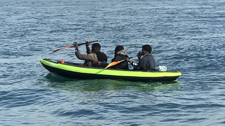 Different boat to Main copy - 3 men in an inflatable boat Re:Migrants - manhandling a large inflatable boat down a northern French beach, to get to the seafront in order to to cross the Channel. - re copy from Adam Parsons and Sophie Garratt