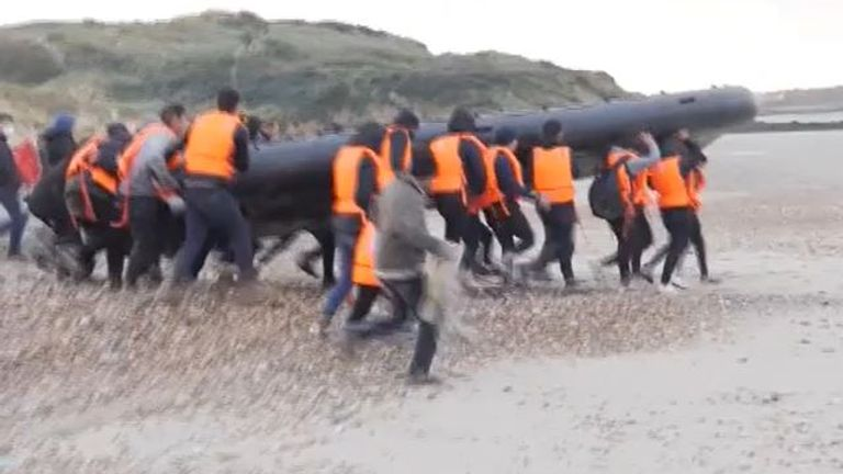 Migrants carry a dinghy to the Channel on Calais beach
