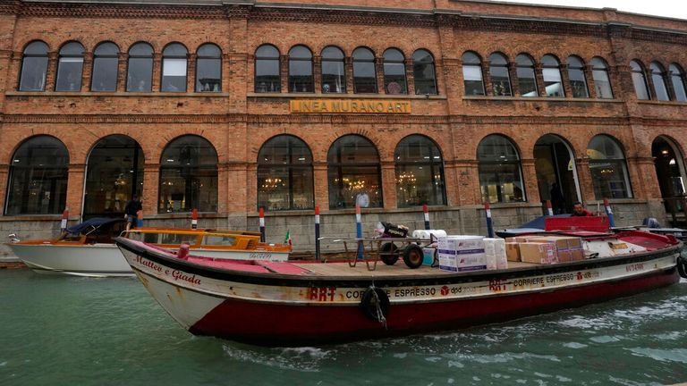 A boat sails past a historical artistic glass factory in Murano island, Venice. Pic: AP