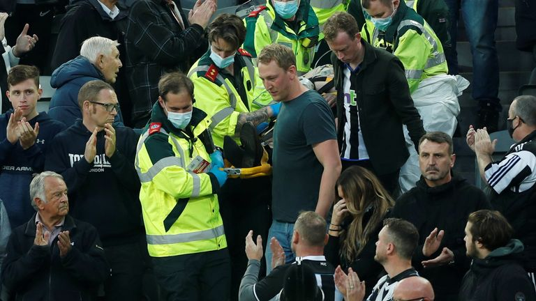 Soccer Football - Premier League - Newcastle United v Tottenham Hotspur - St James' Park, Newcastle, Britain - October 17, 2021. Picture taken October 17, 2021 A Newcastle fan is stretchered away from the stands by paramedics and Dr Tom Prichard, who performed CPR to the man Action Images via Reuters/Lee Smith EDITORIAL USE ONLY.