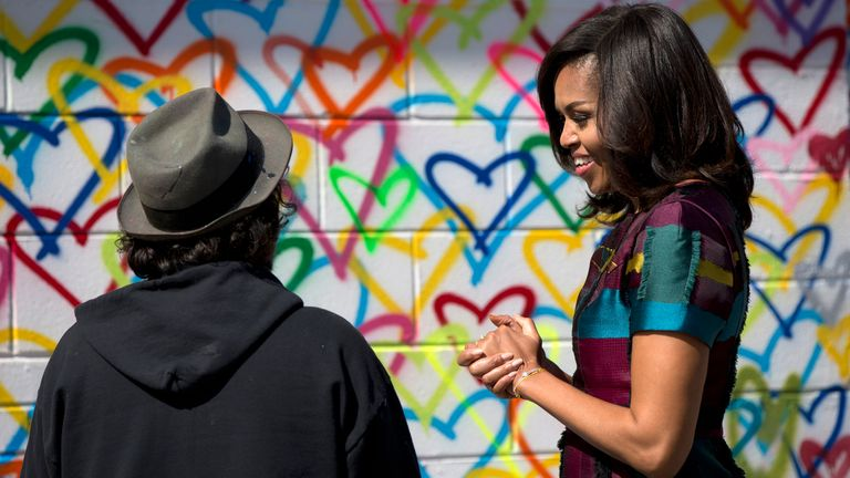 First lady Michelle Obama looks to artist Mr. Brainwash during a live painting of a Let Girls Learn mural at Union Market in Washington, Tuesday, March 8, 2016. Pic: AP