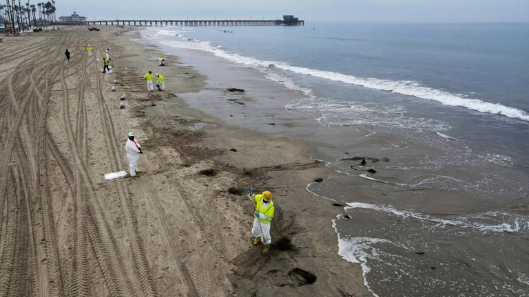 Workers rake up crude oil, after more than 3,000 barrels (126,000 gallons) of crude oil leaked from a ruptured pipeline into the Pacific Ocean in Newport Beach, California