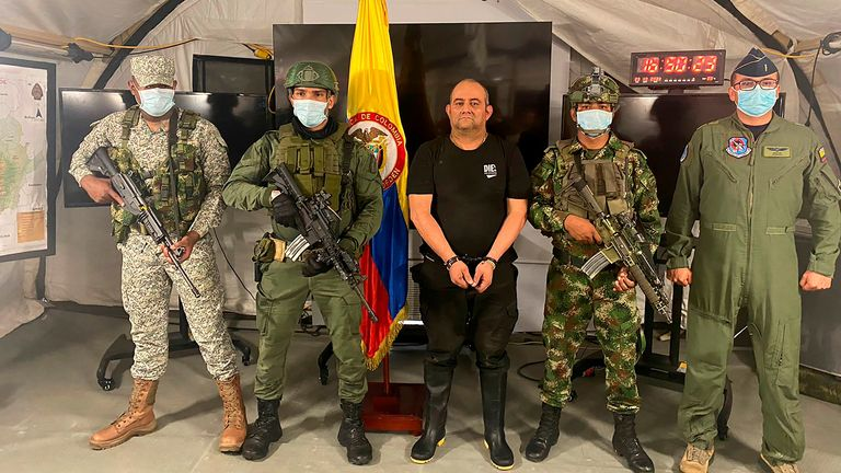 """Dairo Antonio Usuga David, alias """"Otoniel"""", top leader of the Gulf clan, poses for a photo escorted by Colombian military soldiers after being captured, in Necocli, Colombia October 23, 2021. Colombia's Military Forces/Handout via REUTERS ATTENTION EDITORS - THIS IMAGE HAS BEEN SUPPLIED BY A THIRD PARTY. MANDATORY CREDIT. NO RESALES NO ARCHIVES."""