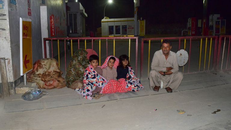 A family gather outside their house following the tremor Pic: AP