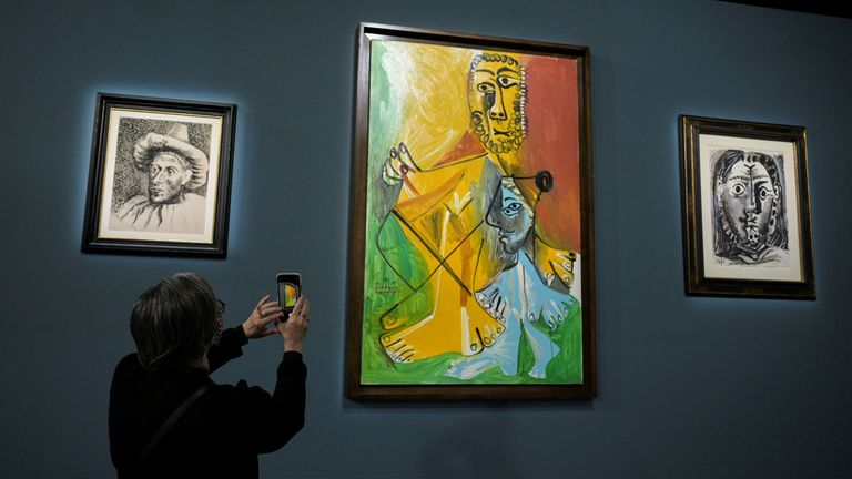 An attendee photographs a painting prior to the auction of 11 Picasso paintings and works at the Bellagio Hotel in Las Vegas, Nevada, U.S. October 23, 2021. REUTERS/Bridget Bennett