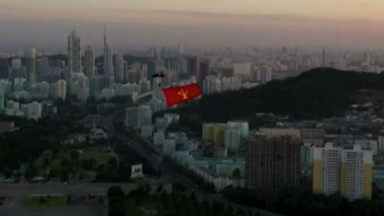 Skyline of Pyongyang with North Korean flag being flown by parachustist