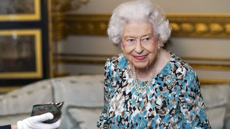 Queen Elizabeth II looks at the Birmingham 2022 Commonwealth Games Baton that will carry a message from her during a relay which starts at Buckingham Palace in London before 7,500 bearers take the baton on a 90,000-mile journey to all 72 nations and territories of the Commonwealth over 294 days. Picture date: Monday October 4, 2021.