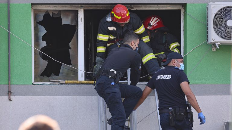 Romania Hospital Fire Emergency personnel exit through a window after a fire in the COVID-19 ICU section of the Hospital for Infectious Diseases in the Black Sea port of Constanta, Romania, Friday, Oct. 1, 2021. Authorities say a fire at a hospital in Romania's port city of Constanta has killed nine COVID-19 patients in the ICU. All patients have been evacuated following Friday's blaze at Constanta's Hospital for Infectious Diseases. (AP Photo/Costin Dinca) PIC:AP
