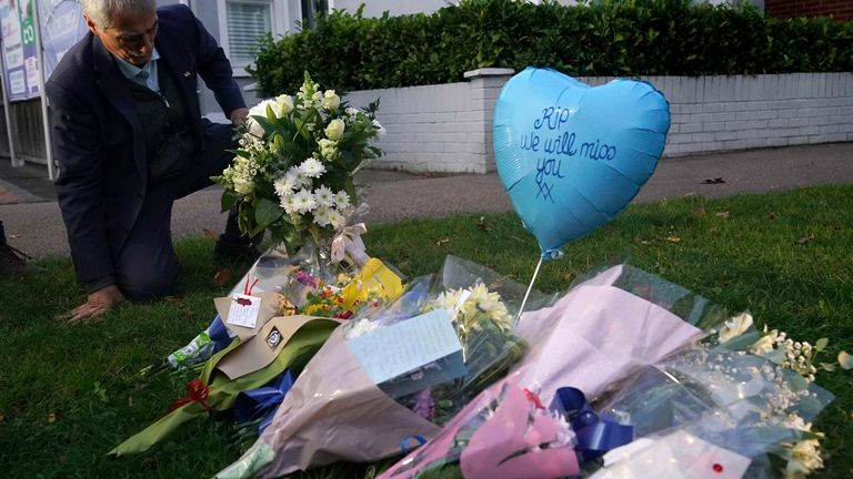 A man lays flowers at the scene near the Belfairs Methodist Church in Eastwood Road North, Leigh-on-Sea, Essex, where Conservative MP Sir David Amess has died after he was stabbed several times at a constituency surgery. A man has been arrested and officers are not looking for anyone else. Picture date: Friday October 15, 2021.