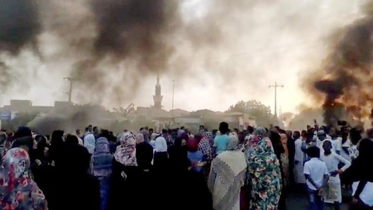 People gather on the streets as smoke rises in Khartoum, Sudan, amid reports of a coup,