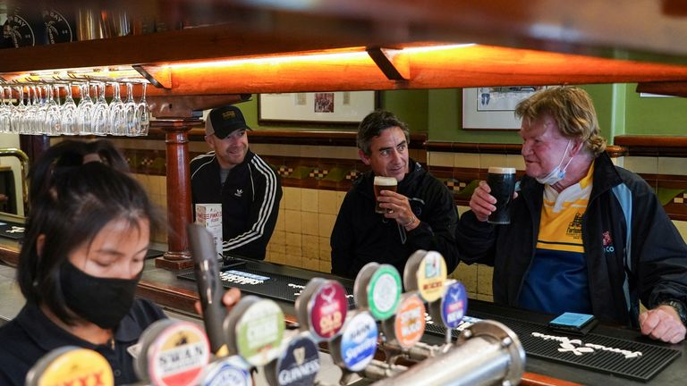 Customers Brian O'Mara, Darrell Forman and Doug Thomas drink beers together at the Fortune of War pub, on the first morning of pubs and many other businesses re-opening to vaccinated people, following months of lockdown orders to curb an outbreak of the coronavirus disease (COVID-19), in Sydney, Australia, October 11, 2021. REUTERS/Loren Elliott