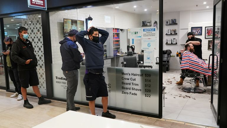 Customers wait in line at a city centre barber shop on the first day of many such businesses re-opening to vaccinated patrons, following months of lockdown orders that closed businesses to curb an outbreak of the coronavirus disease (COVID-19), in Sydney, Australia, October 11, 2021. REUTERS/Loren Elliott
