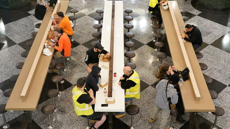 Diners sit to eat at a city centre food court on the first day of eased restrictions for vaccinated patrons, following months of lockdown orders that mandated restaurants only serve take-away and customers couldn't sit to eat at such venues to curb an outbreak of the coronavirus disease (COVID-19), in Sydney, Australia, October 11, 2021. REUTERS/Loren Elliott