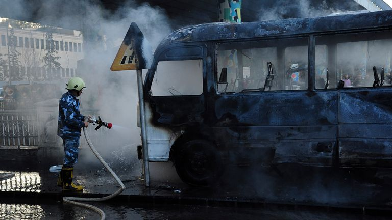In this photo released by the Syrian official news agency SANA, shows a Syrian firefighter extinguishes a burned bus at the site of a deadly explosion, in Damascus, Syria, Wednesday, Oct. 20, 2021. Two roadside bombs exploded near a bus carrying troops during the morning rush hour in the Syrian capital early Wednesday, killing and wounding several people, state TV reported.(SANA via AP)