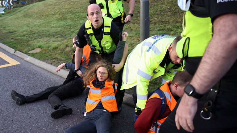 Police officers remove Insulate Britain activists as they block a roundabout at a junction on the M25 motorway during a protest in Thurrock, Britain October 13, 2021. REUTERS/Henry Nicholls