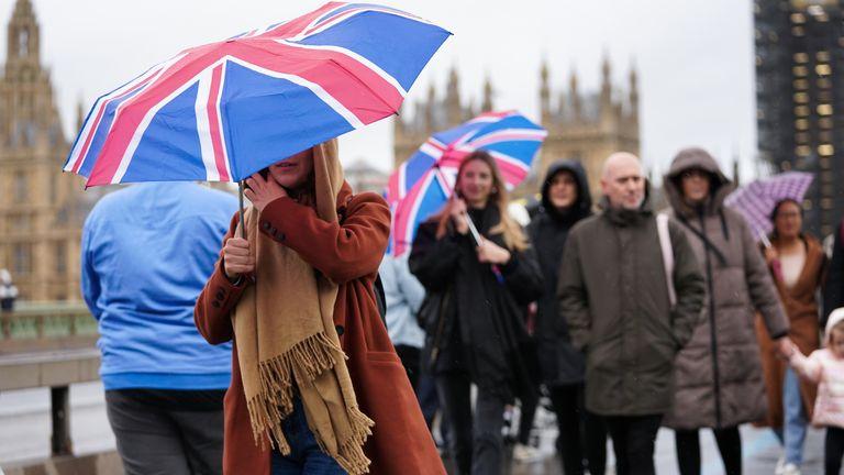 People walk across Westminster Bridge in the rain, in Westminster in London