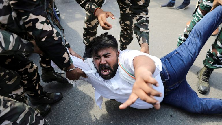 Police forces detain a man during a protest in New Delhi