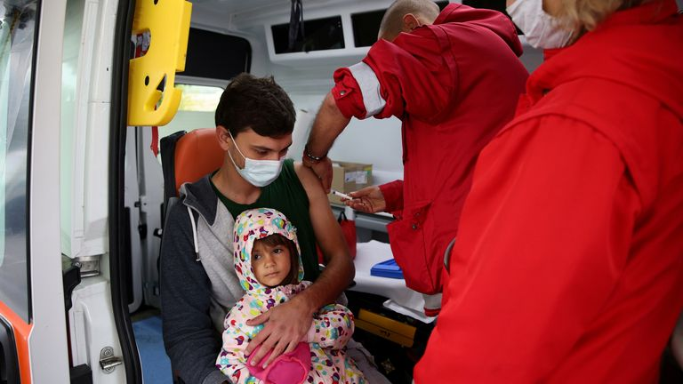 A man holds his daughter, as he receives a second dose of vaccine against the coronavirus disease (COVID-19) administered by a medical personnel from a mobile unit in the village of Krushovitsa, Bulgaria, October 10, 2021. REUTERS/Stoyan Nenov/File Photo