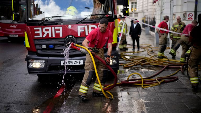 A fire fighter pulls pumping hoses out from the flood damaged Azagury women's fashion designer store after heavy rain in the upmarket Knightsbridge district of central London, Tuesday, Oct. 5, 2021. (AP Photo/Matt Dunham) PIC:AP