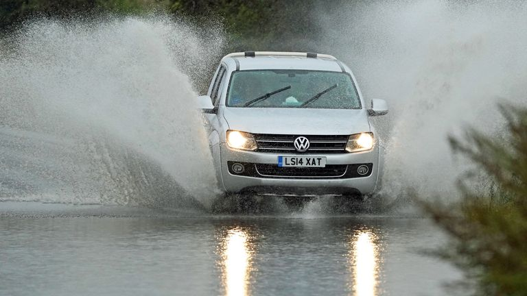 A car goes through floodwater in Whitley Bay, in North Tyneside
