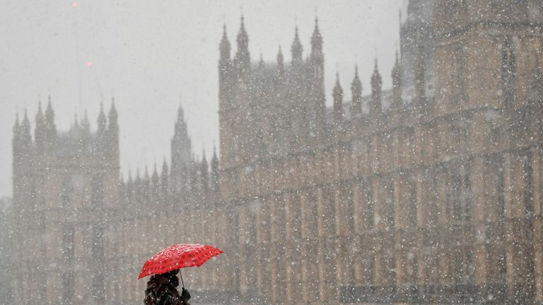 A person crosses the Westminster Bridge, with the Palace of Westminster on the background, as snow falls in London, Britain, January 24, 2021. REUTERS/Toby Melville