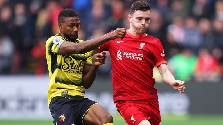 Emmanuel Dennis of Watford and Andrew Robertson of Liverpool battle for possession