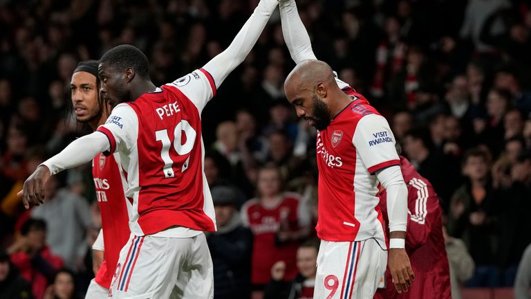 Arsenal's Nicolas Pepe, 2nd left, raises the term of team mate Alexandre Lacazette after he scored his side's second goal, the equalizer, during an English Premier League soccer match between Arsenal and Crystal Palace at the Emirates Stadium in London, England, Monday Oct. 18, 2021. (AP Photo/Alastair Grant)